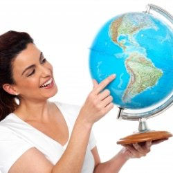 Woman holding a globe and pointing at a country