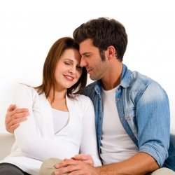 Husband and wife hug on couch