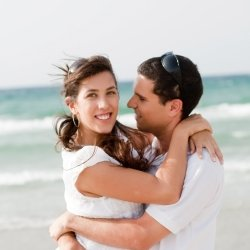 Husband and wife hugging on beach