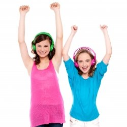 Cousin sisters listening to music on headphones and arms raised