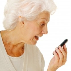 Elderly woman reading text message on cell phone