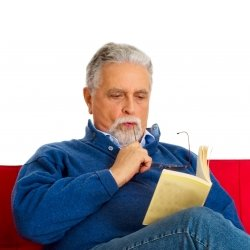 Old man sitting on a red sofa and reading a book