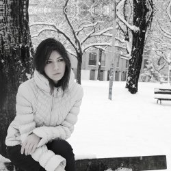 Lonely girl sitting alone on a park bench while it is snowing