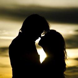 Girlfriend and boyfriend hugging against sunset
