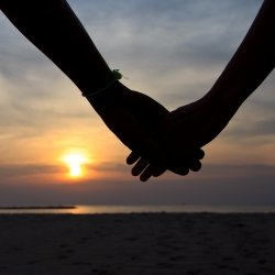 Couple holding hands against beautiful sunset