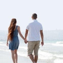 Couple holding hands and walking down the beach