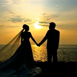 Married couple standing against the sunset