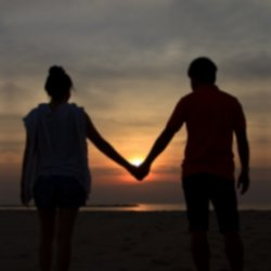Couple holding hands against a beautiful sunset