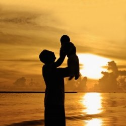 Father holding his son his arms on the beach against a beautiful sunset