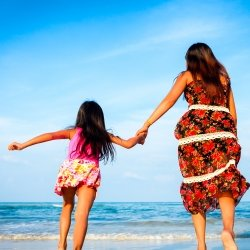 Little daughter holding her mother's hand on the beach