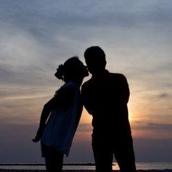 Girl kissing her boyfriend against the sunrise