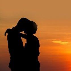 Couple hug against sunset