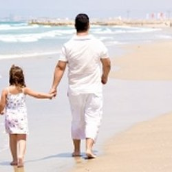Girl holding daddy's hand while walking on the beach