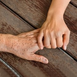 Young child's hand holding old grandparent's hand