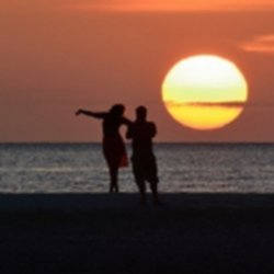 Couple standing against sunset