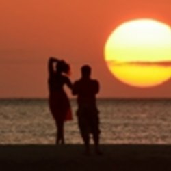 Couple standing on the beach against sunset